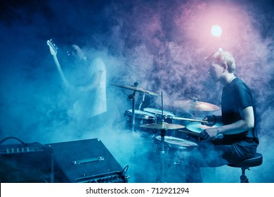 The drummer plays solo. Rock concert. Scene. Smoke Stage light.