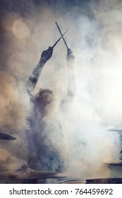 Drummer posing surrounded by fog