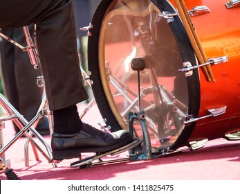 drummer's foot is on the pedal and beats the drum