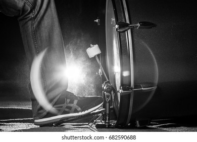 The drummer's foot wears sneaker is playing bass drum pedal in low light background, black and white