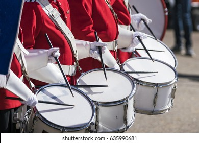 Drummers in red uniforms on a row at a spring parade with white gloves drumming on drums