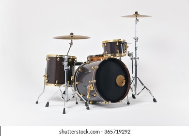 Drums of 7 elements of cinnamon and black with gold-plated fittings , photographed on a white background