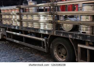 Drums being carried by a truck on a business day. Steel drums can be seen loaded onto the carrier for transporation. The drums seem to be carrying something liquid.