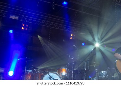 drums on stage with white orange and blue colors from lamps