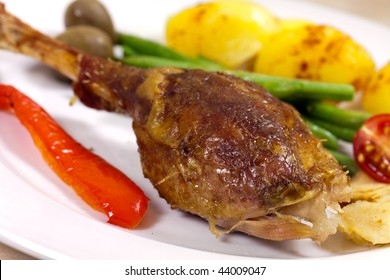 Drumstick of baked Goose with green beans,potatoes,apple,pepper