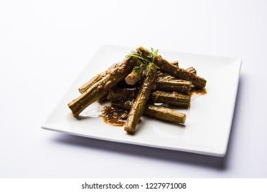 Drumstick masala or Shevga sheng sukhi sabji, served in a plate over moody background. Selective focus