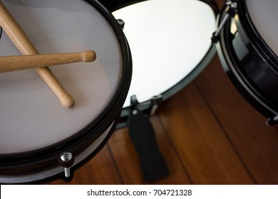 Drumstick, snare drum, floor drum, bass drum and drum pedal on the wood floor.