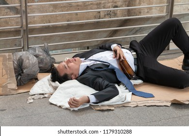 Drunk Asian businessman holding a bottle of alcohol and sleeping on dirty cardboard on the sidewalk. Unsuccessful businessman drunk and unconscious on public walkway.