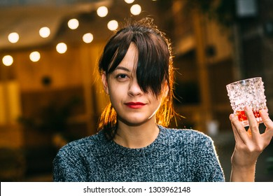 Drunk brunette student woman alone in happy smiling face expression holding and looking thoughtful to scotch whiskey glass at bar or pub in alcohol abuse and alcoholic concept.