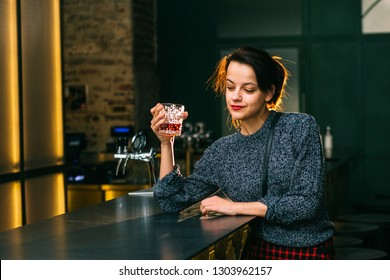 Drunk brunette student woman alone in depressed face expression looking thoughtful in pub or night club. Desperate girl binge drinking to forget problems glass of scoth whiskey alcohol.