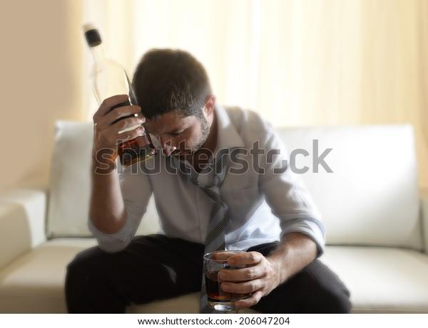 hombre de negocios ebrio en casa durmiendo en el sofá durmiendo perdido sosteniendo el whisky de vidrio en el interior en problema de alcoholismo, abuso de alcohol y el concepto de adicción parecen desordenados y enfermos