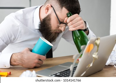 drunk businessman with bottle of champagne at workplace in office