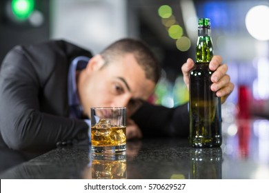 Drunk businessman slumped on bar beside drink