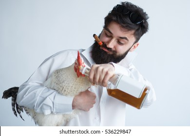 drunk crazy man with chicken. Bearded man tries to give alcohol to a chicken cock