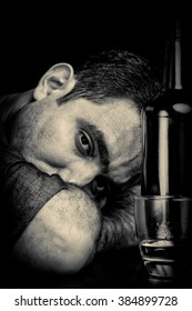 Drunk and depressed man with a sad face drinking alone