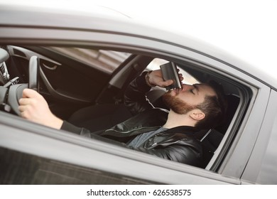 Drunk driver driving a car. Driving in a state of intoxication.Young man driving a car with an iron flask with alcohol.