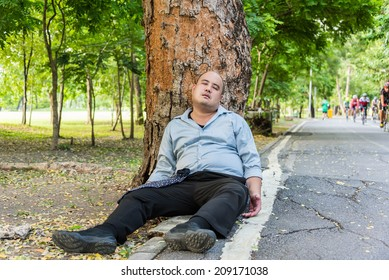 A drunk fat bald head Asian man is sleeping under the tree beside the street. The concept is that he could be drunk, having a heart attack, sleeping or to tired from office workload.