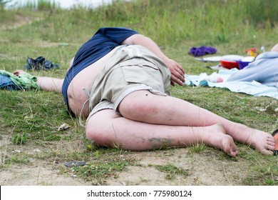 Drunk fat man lies on the ground in nature, the theme of alcoholism and wrong lifestyle