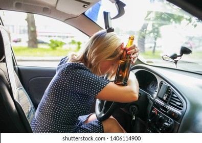 drunk girl driving a car. Girl drinks alcoholic beer from a bottle while driving