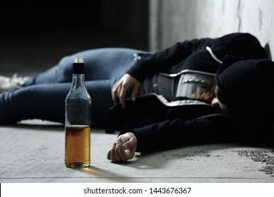 Drunk girl sleeping on the floor in a garage with a bottle of alcohol drink in foreground