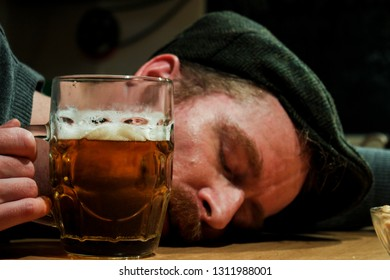 Drunk guy with beer in hand sleeping on the bar