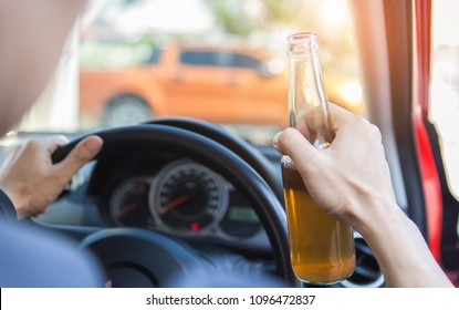 Drunk hand man driving a car with a bottle of beer. Don't drink and drive concept.