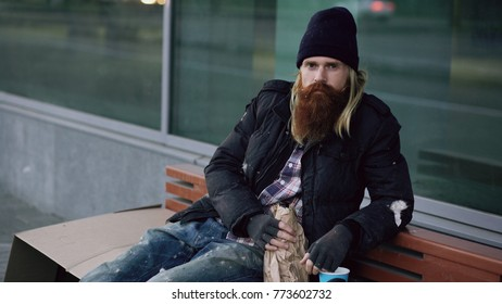 drunk homeless sleepy man smiling and looking at the camera while sitting on bench at the sidewalk