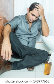 Drunk latin man suffering a hangover and sitting on the toilet floor
