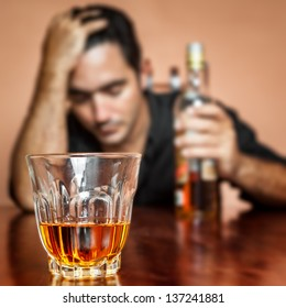 Drunk and lonely latin man holding a rum or whiskey bottle (image focused on his drink)