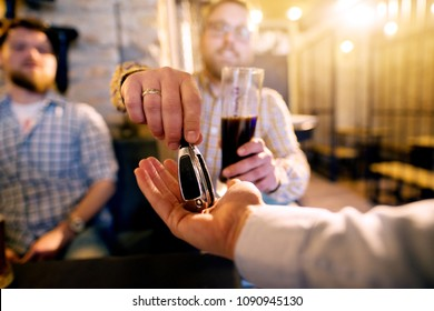 Drunk man with a beer in hand giving car key to the sober friend while enjoying in the bar. Close up focus view of key and hands.