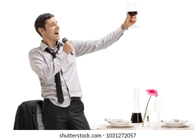 Drunk man holding a glass of wine and singing on a microphone isolated on white background