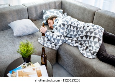 Drunk man lying on the couch covered with blanket, suffering from the alcoholism at home