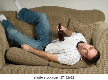 A drunk man is passed out on the couch from drinking too much beer