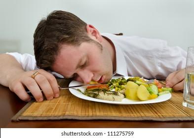 Drunk man sleeping in his dinner plate
