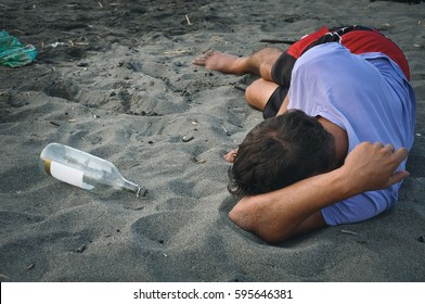 Drunk man sleeping on the sand at the beach
