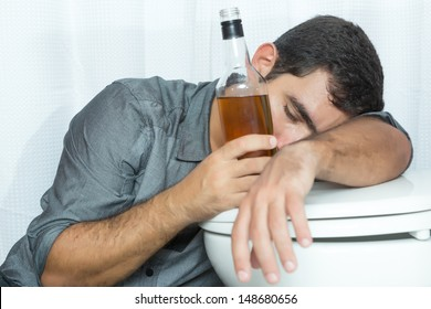 Drunk man sleeping on the toilet and holding a liquor bottle