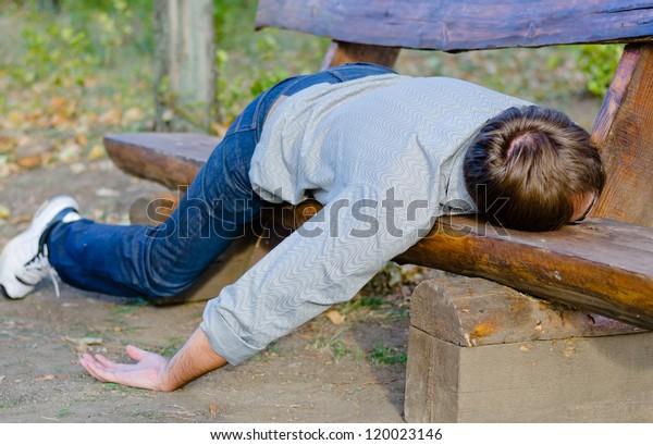 Drunk man sleeping in park on wooden bench