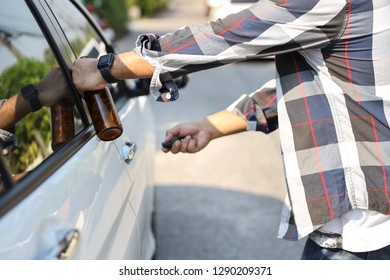 drunk man try opening vehicle with car key while holding alcohol bottle in another hand (drink not drive concept)