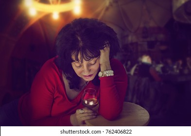 Drunk mature woman in red jumper leaning on wooden stool sadly looks down into a glass of brandy. Dark indoors cafe blurred background