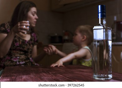 Drunk mother with alcoholic drink scolding her little son. Alcohol abuse, Female alcoholism. Focus on bottle.