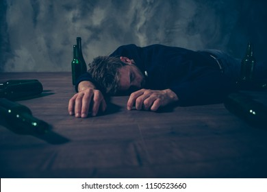 Drunk people person concept. Low angle close up view photo portrait of tired exhausted unconscious guy lying sleeping on floor surrounded by empty bottles