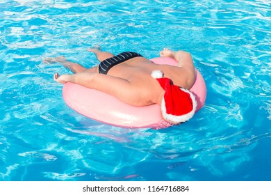 drunk resting guy in santa claus hat on the inflatable circle in the swimming pool of the hotel.