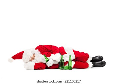 Drunk Santa Claus lying on the ground with a few beer bottles around him isolated on white background