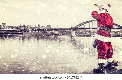 Drunk Santa Claus watching the city from river side