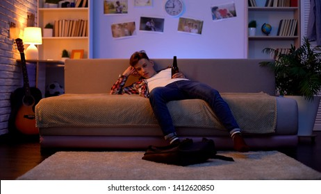 Drunk teen student sitting on sofa with beer bottle, harmful alcohol addiction