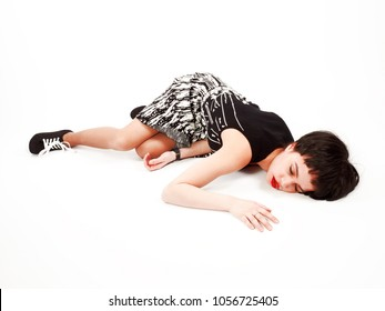 Drunk teenager in a whimsical pose on the floor on a light background