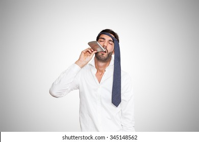 Drunk and tired young business man with tie around the head, on gray background.