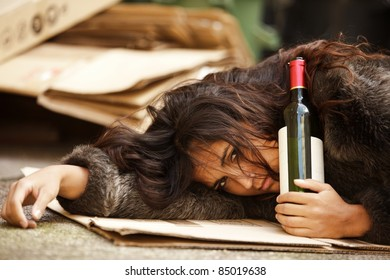 drunk tramp woman holding bottle of wine and lying on pavement