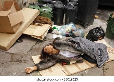 drunk tramp woman lying on cardboard in city trash area