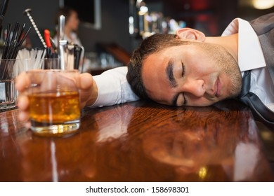 Drunk and unconscious businessman lying on a counter in a classy bar